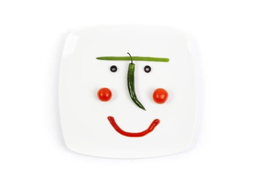 while plate with coloful vegetables making a smiley face