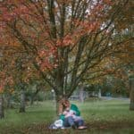Women breastfeeding her baby near a tree