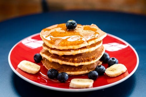 Pancakes with syrup, blueberries and bananas