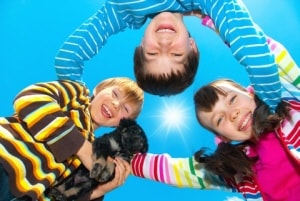 3 school age kids huddled around looking happy with a blue sky and sun shining