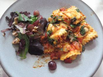 Ravioli with spinach and sun-dried tomatoes on a plate with a salad