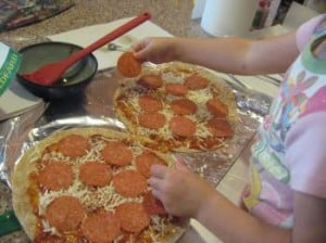topping the tortilla with cheese and pepperoni