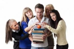 teen girls surrounded a boy holding a stack of books topped with an apple