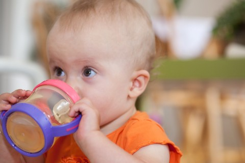 baby holding and drinking out of a sprout sippy cup