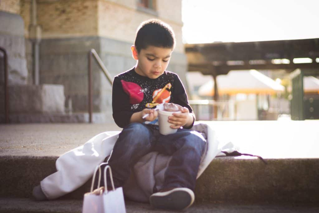 a boy sitting down outside eating a bowl of food