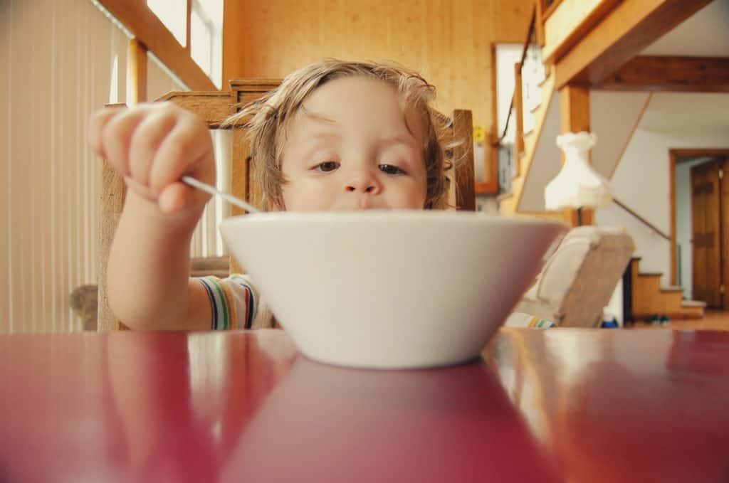 Girl eating a bowl of food at the kitchen table
