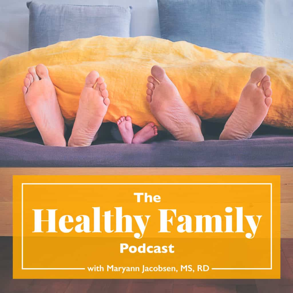 family of three under the covers and feet showing